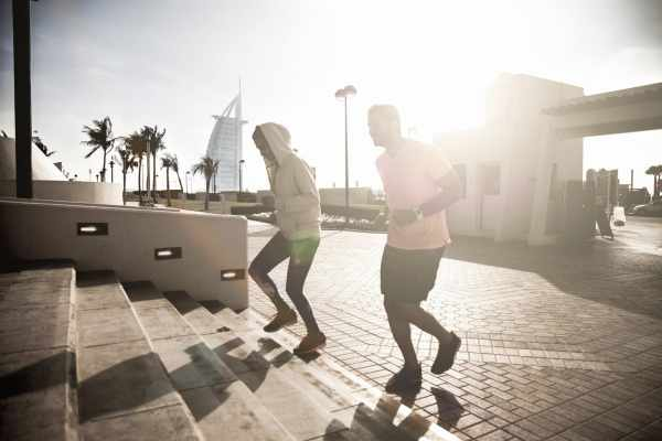 Young athletic couple exercising on steps in Jumeirah Beach promenade in Dubai, UAE. The two guys starting a fitness run on the sidewalk.