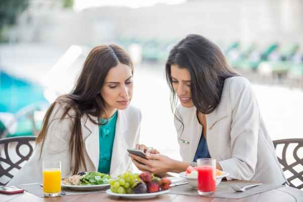 Two female friends eating breakfast and viewing cellphone
