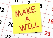 A reminder to Make A Will in red text on a yellow sticky note posted on the page of a calendar or planner