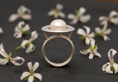 white pearl ring in silver with halo design