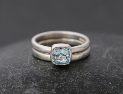 Sparkly cushion cut aquamarine engagement ring in silver with matching wedding band
