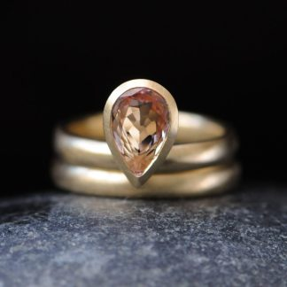 Pale pink pear cut morganite engagement ring with matching wedding band in gold