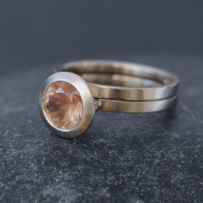 peach colour naturally faceted oregon sunstone set in gold engagement ring, with matching wedding ring