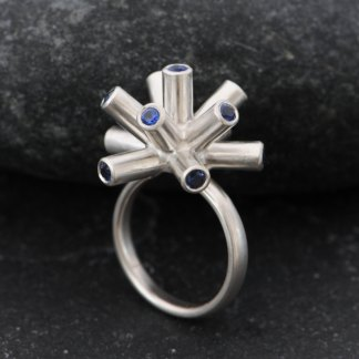 Particle Collider ring in silver with 11 blue sapphires