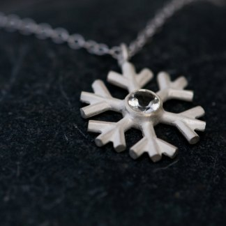 White topaz snowflake, set in sterling silver on a fine silver necklace. By William White
