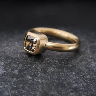 chocolate diamond solitaire ring in gold on dark background