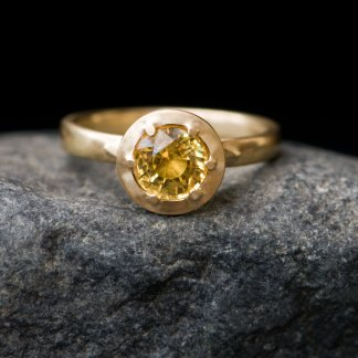 Gold ring with claw set yellow sapphire on grey rock