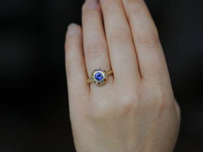 tanzanite button ring on hand