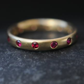ruby eternity band in 18K Y gold