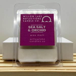packaged soy wax melt sitting on wood with grey background purple label