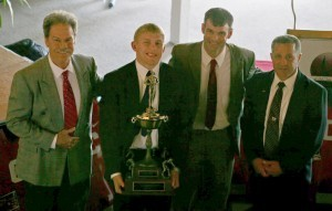 Kyle Dake (second from left) received the Hodge Trophy from WIN publisher Bryan Van Kley (second from right) and ASICS Neil Duncan (left) and Nick Gallo.
