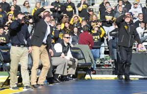 Iowa coach Tom Brands (right) and his staff looked up at the large scoreboard to check out his team's success vs. Oklahoma State (Ginger Robinson photo)
