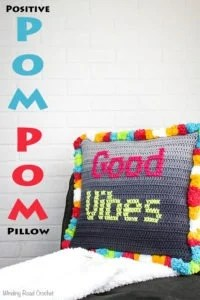 The Positive pom pom pillow is a easy and fun crochet project that uses cross stitch and red heart's pompadoodle yarn to create a fun and festive crochet pattern. This free crochet pattern is great for beginners because it uses very basic stitches to create a creative pillow. #crochetpattern #freecrochet #crochetpillow #pillow #homedecor