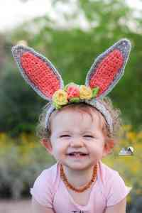 Crochet bunny ear headband with flowers for a child in your life. This is the perfect accessory for easter and spring photos. This free crochet pattern will walk you through the steps to make this baby headband. #crochetheadband #eastercrochet #springcrochet