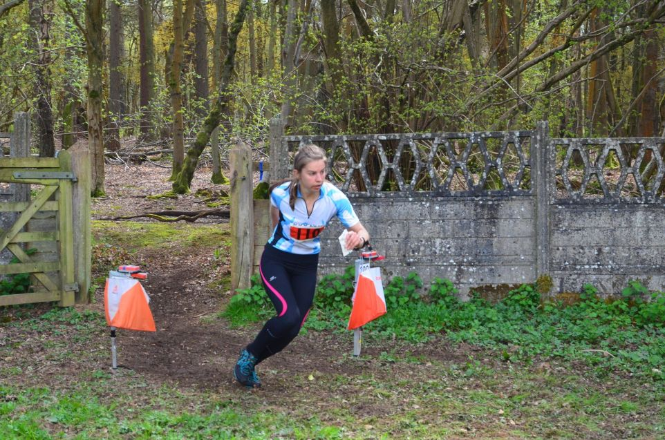 Female orienteer running from control