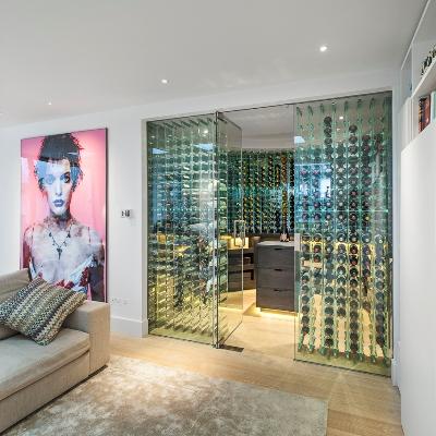 Adega de vidro com espaços para garrafas que vão do chão ao teto. Projeto da Maxwell & Company Architects