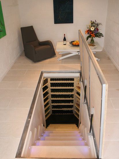 Adega construída em espaço semelhante a um alçapão. Há uma escada escondida em uma tampa no chão da sala de estar que leva à pequena adega.