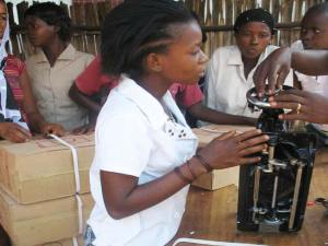 A young women learning how to use a sewing machine