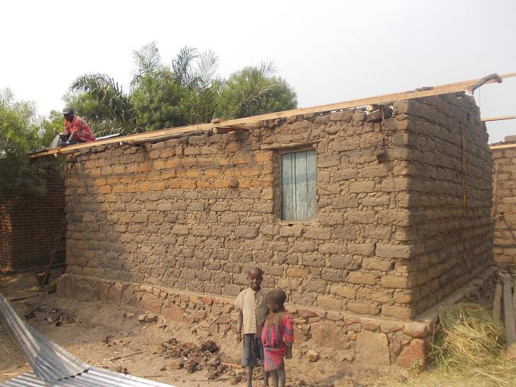 2 young children stand outside a brick house