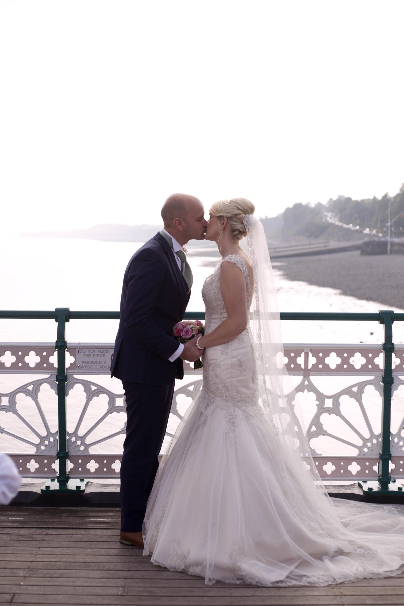 Bride and groom kiss on Penarth Pier Cardiff Wedding Photographer