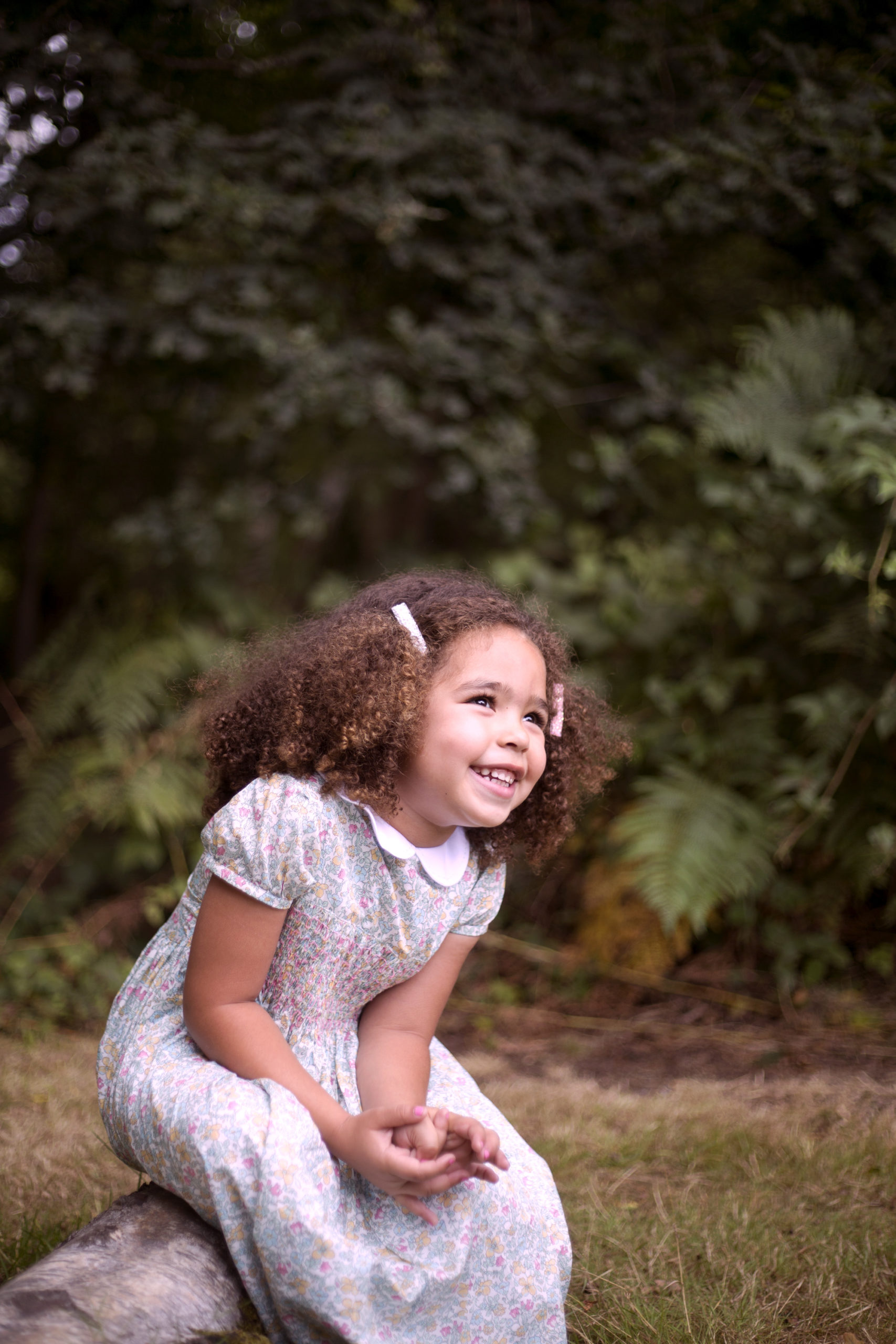 Little guest sitting on a log in woodland wedding photographer