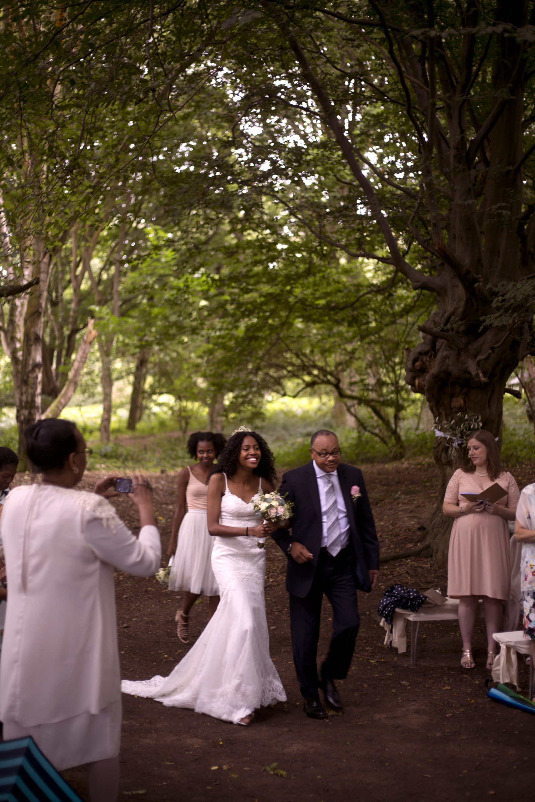 Father of the bride walks the bride down the aisle outdoor ceremony woodland wedding photographer