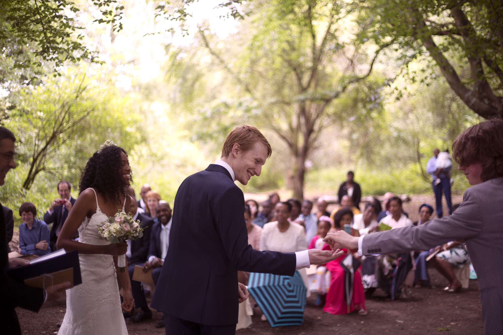 Groom smiles as he takes the rings from the best man woodland wedding photographer