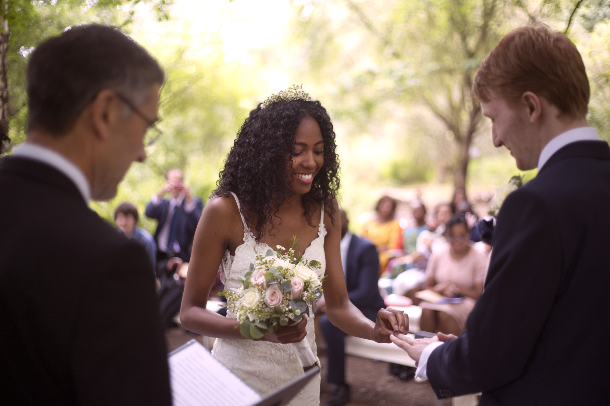 Bride and groom exchanging rings during ceremony outdoor wedding photographer
