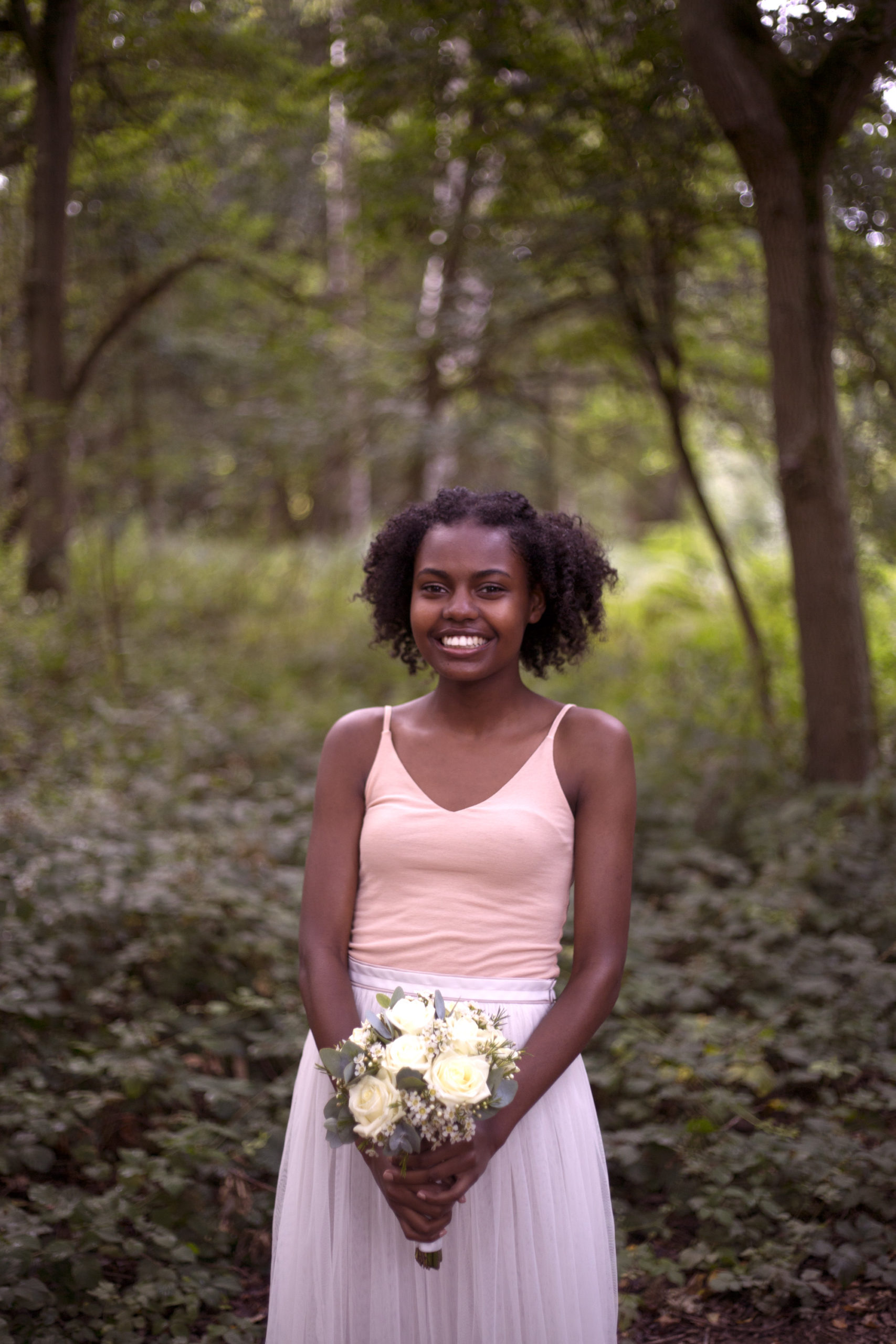 Smiling bridesmaid with cream rose bouquet in woodland wedding photographer