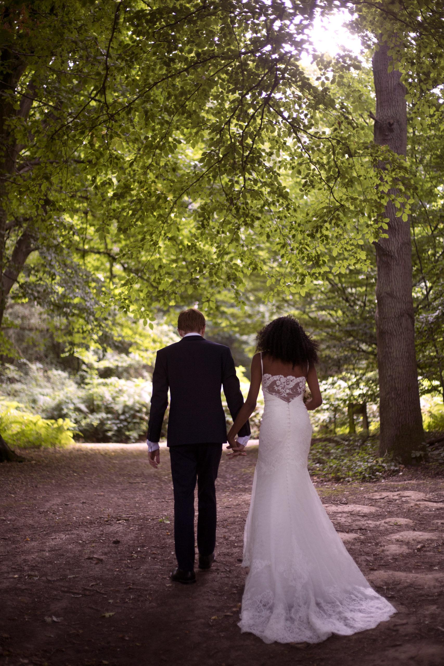 Bride and groom walk under the trees dappled light Cuffley camp outdoor woodland wedding photographer