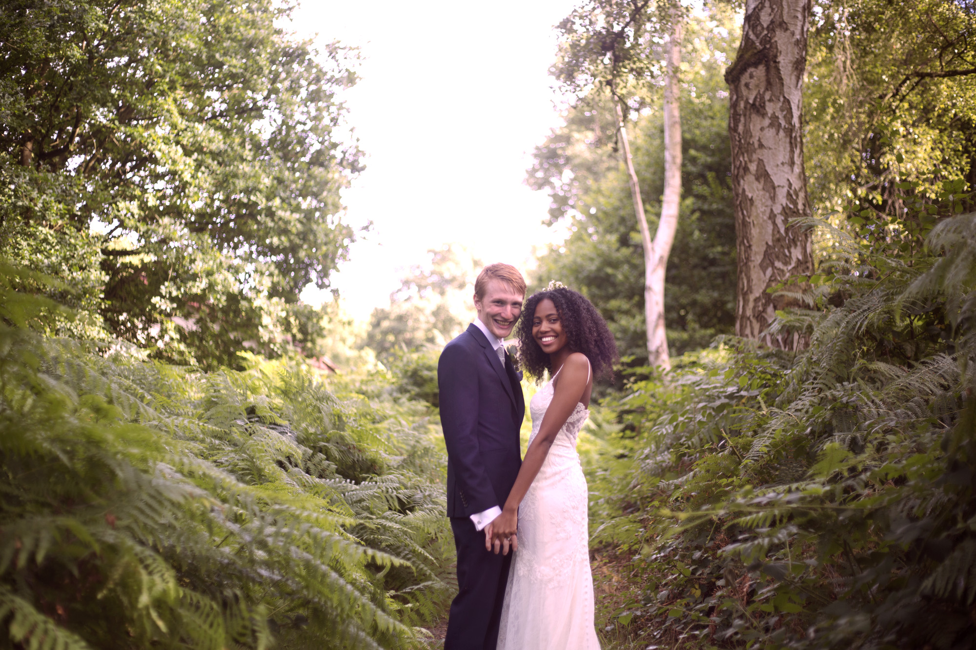 Bride and grooms holding hands in ferns Cuffley camp outdoor woodland wedding photographer