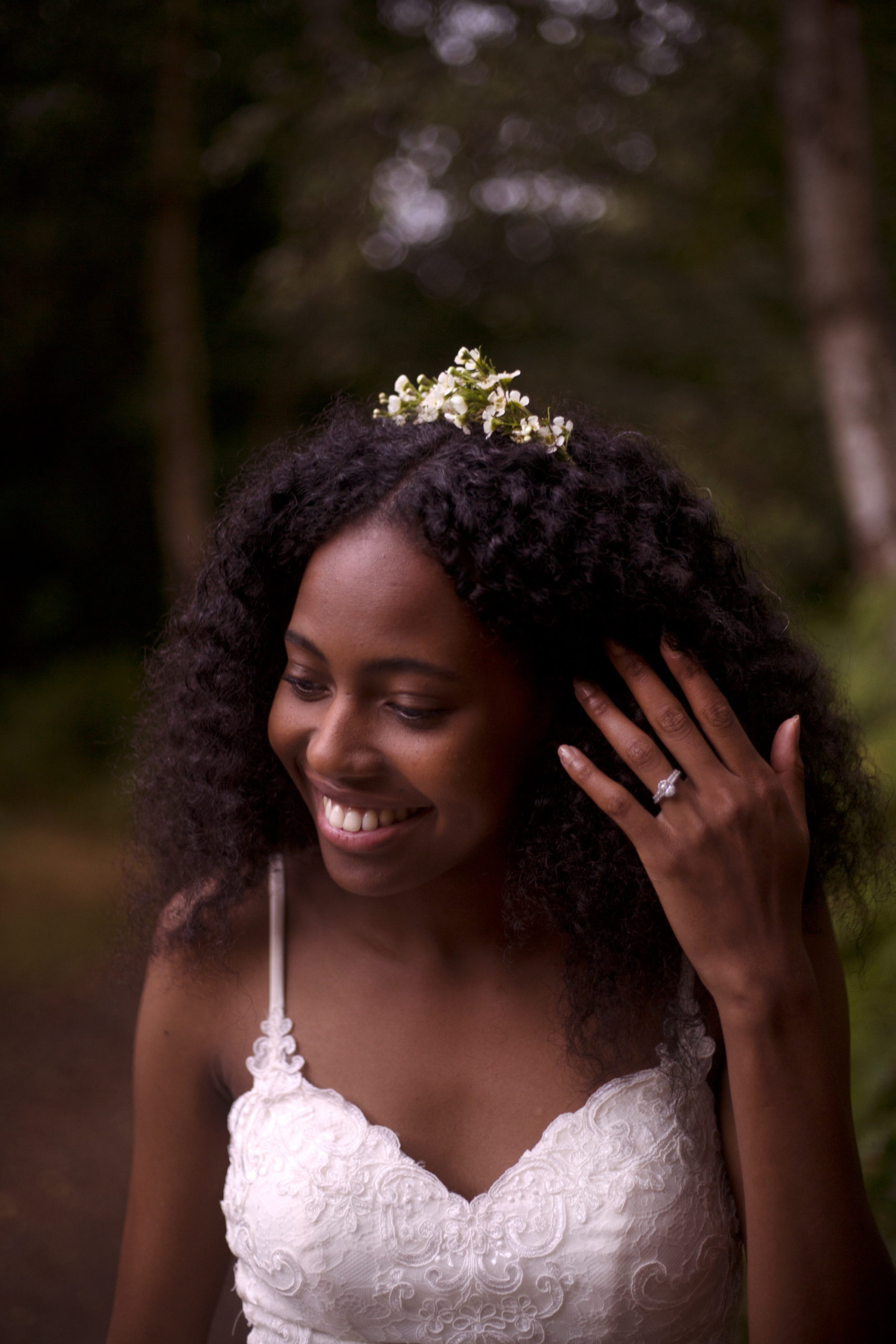 Bride moving her curls to show off her smile and beautiful ring at Cuffley camp outdoor woodland wedding photographer