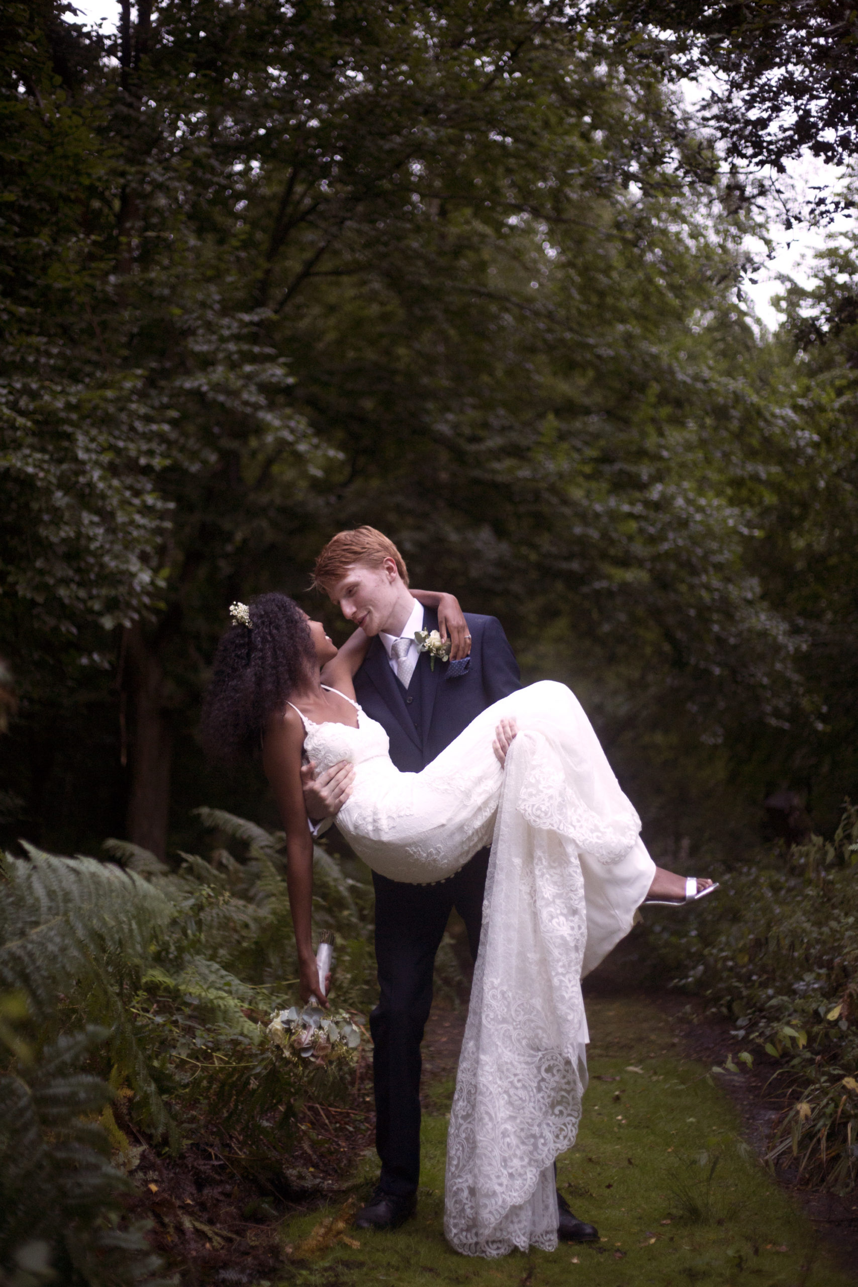 Groom picking up bride in romantic gesture at Cuffley camp outdoor woodland wedding photographer