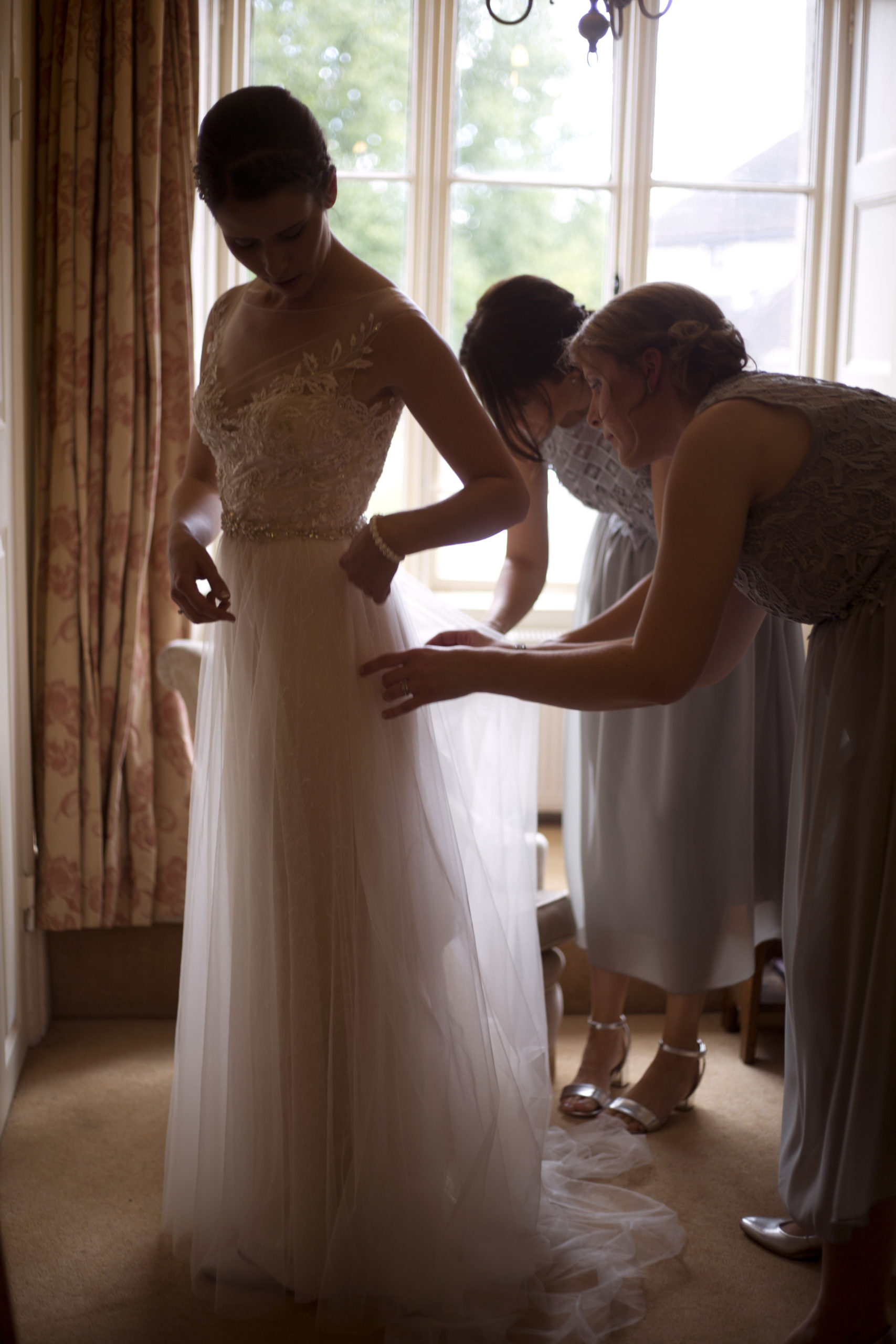 Bridesmaids helping bride into her wedding dress silhouette Cripps barn outdoor wedding photographer