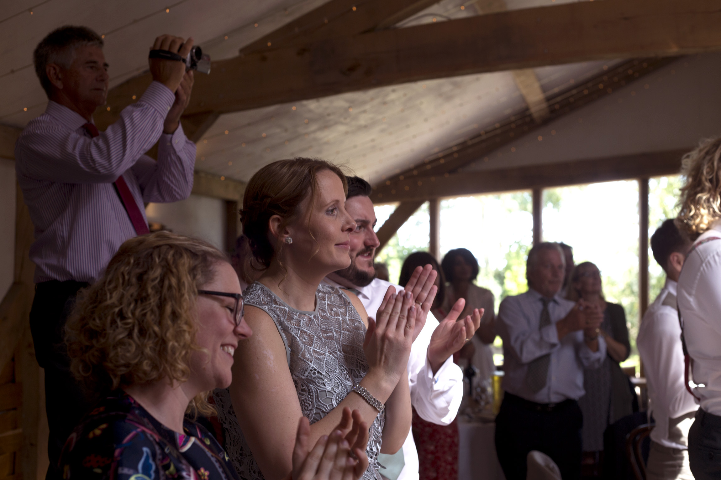Guests clap at speeches Cripps barn outdoor wedding photographer