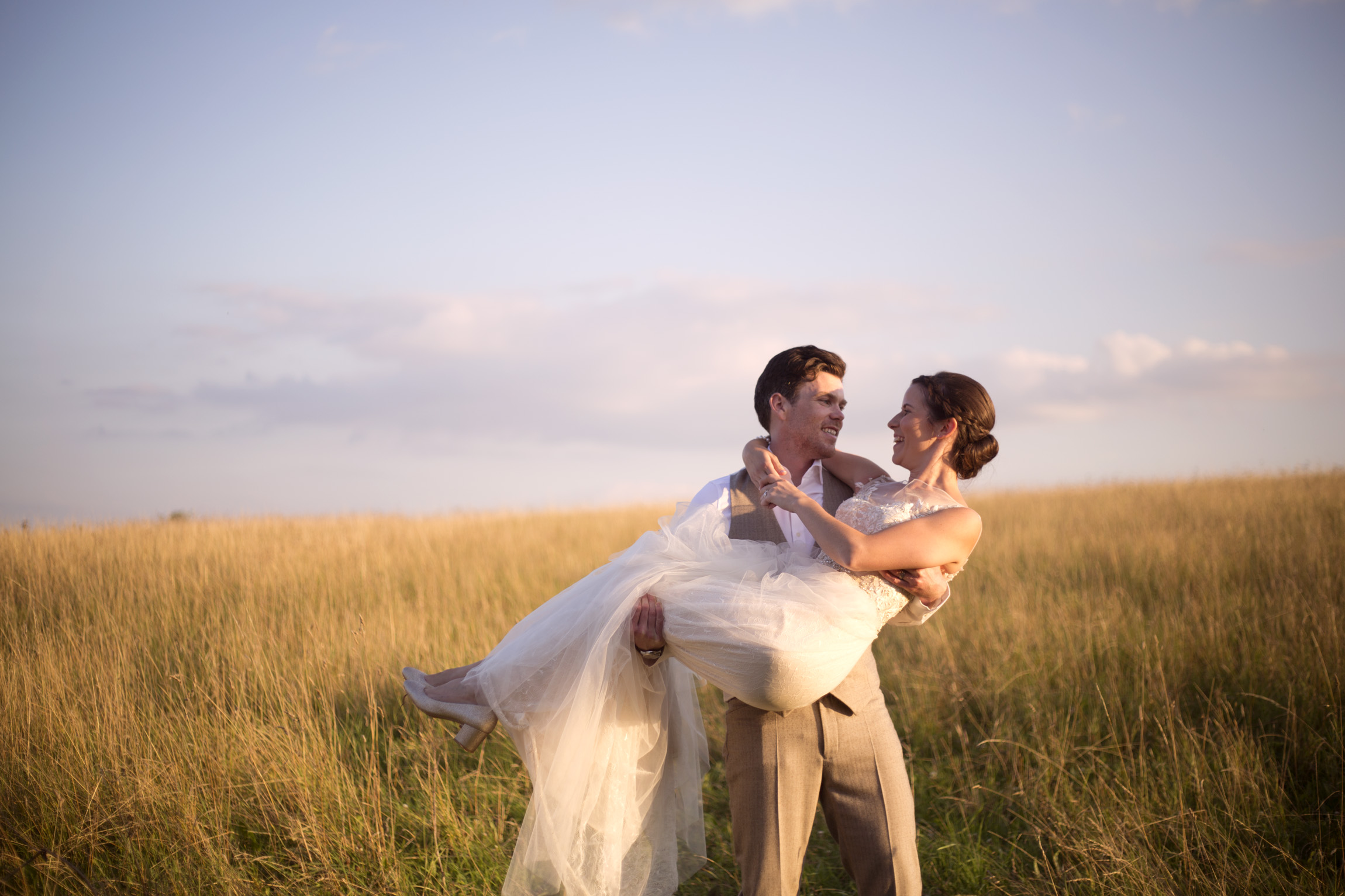 Groom picking up bride sunset golden hour Cripps barn outdoor wedding photographer