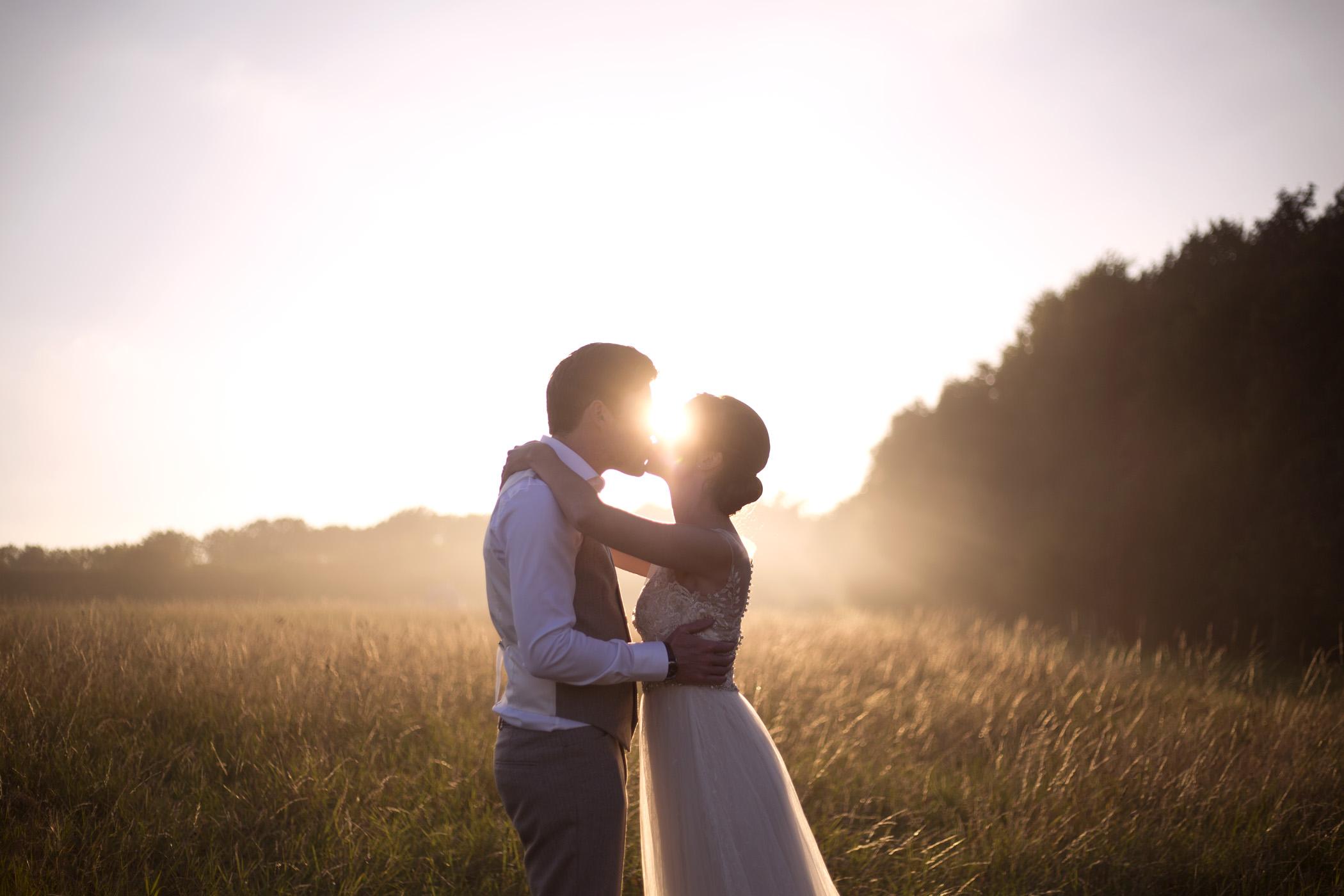 Bride and groom kiss silhouette golden hour sunset Cripps barn outdoor wedding photographer