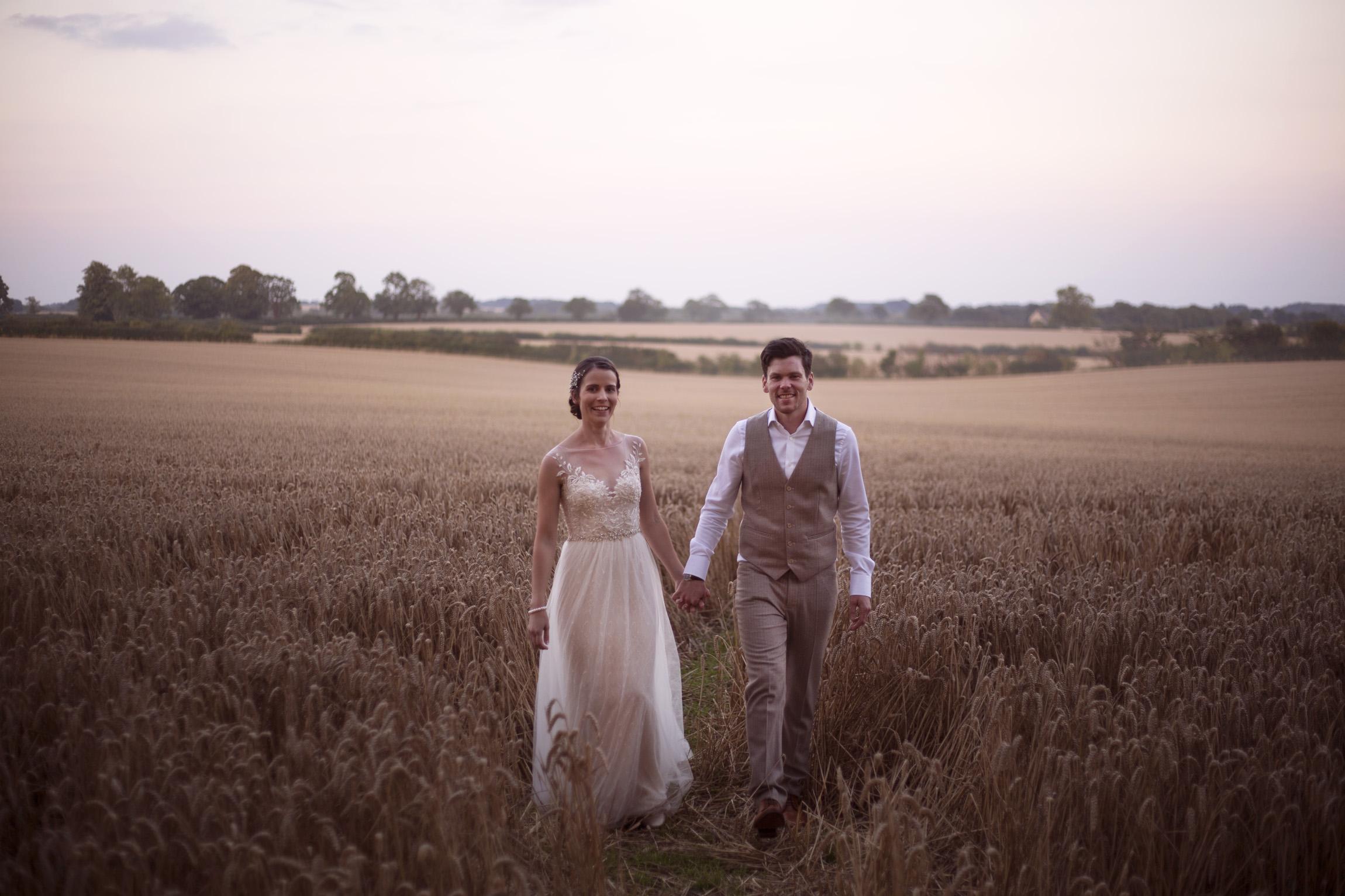 Holding hands bride and groom portrait shoot in cornfield Cripps barn outdoor wedding photographer