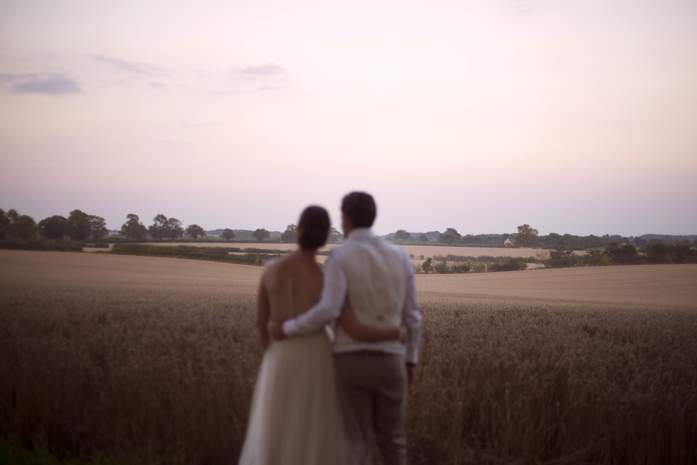 Cuddling bride and groom portrait shoot in cornfield Cripps barn outdoor wedding photographer