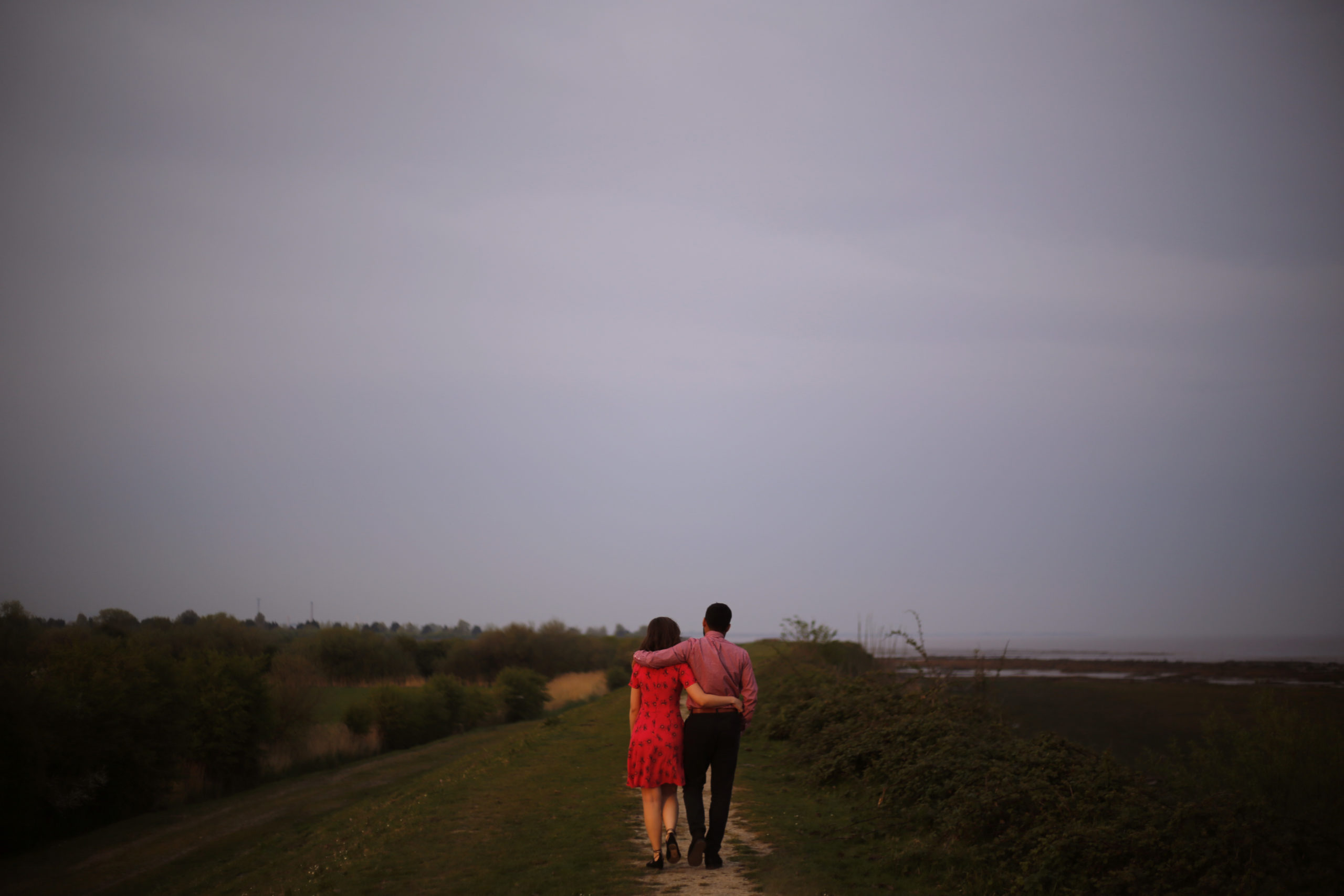 Engaged couple walk arm in arm by the sea on the Wentloog Levels Cardiff