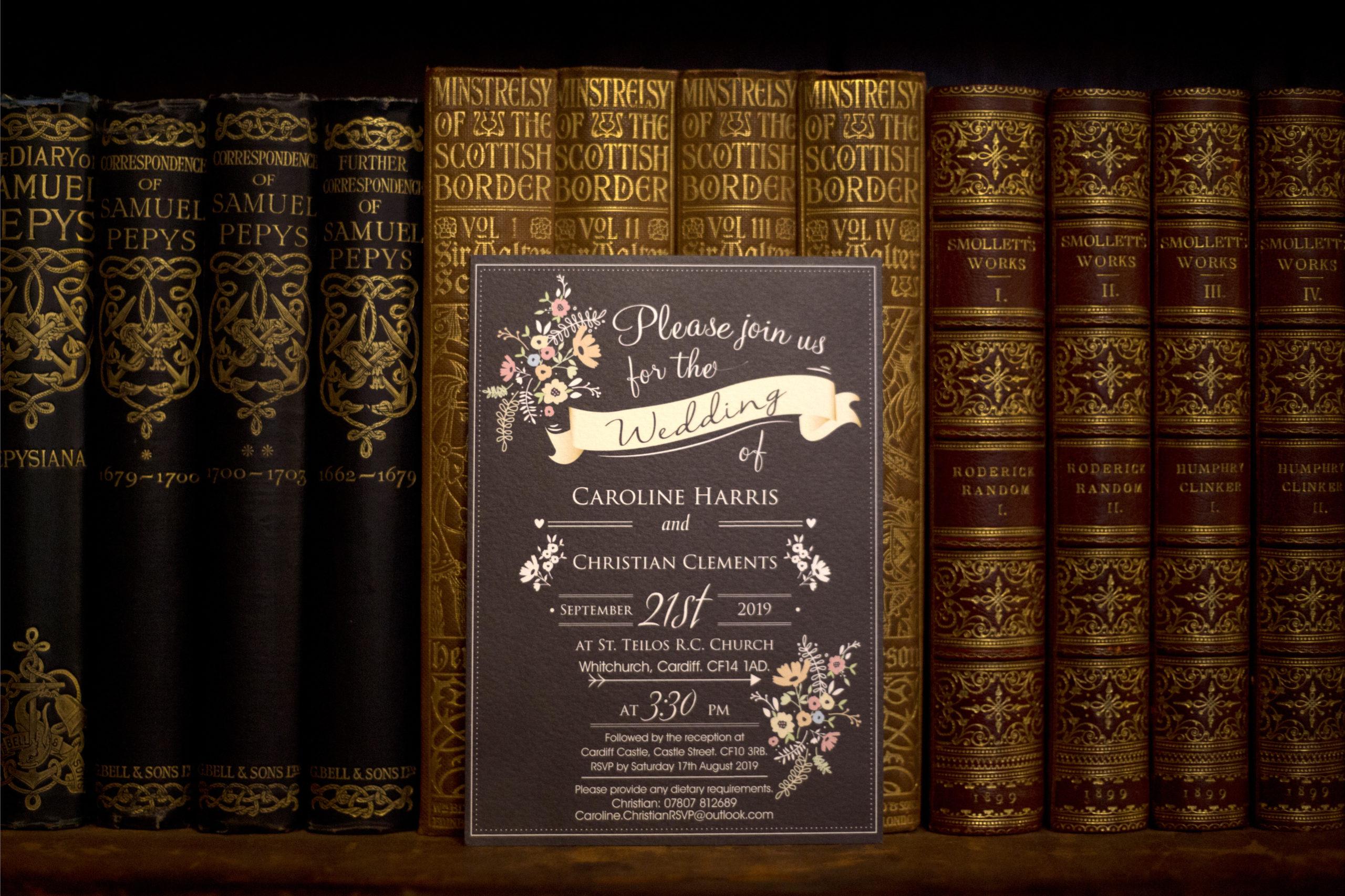 Wedding invitation on bookshelf in library Cardiff Castle Wedding Photographer St Teilos