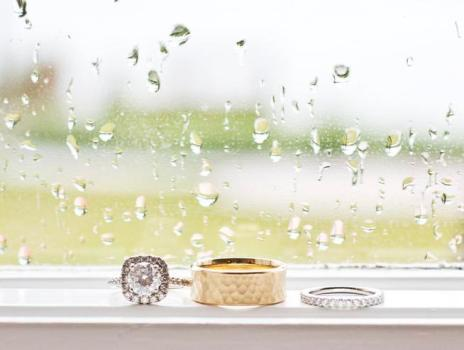 Wedding rings on a window sill with rain falling outside and raindrops on the window