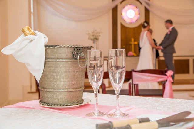 A couple getting married in the background with a close up shot of the Champagne and glasses in the foreground