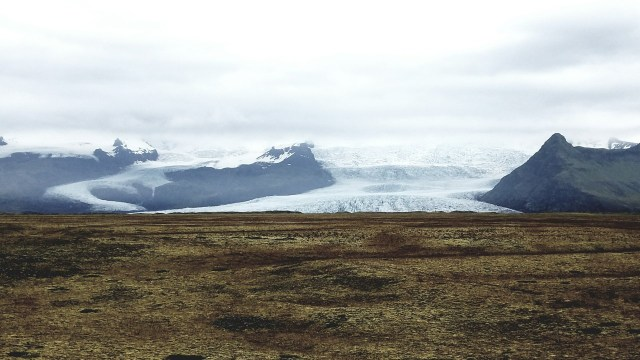 Wide glacier leading onto a grassy plain.