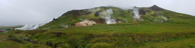 Steam rising from numerous spots in a green landscape