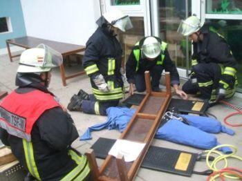 """Mit Hebekissen wurde der """"schwere Balken"""", unter dem die Übungspuppe lag, angehoben und diese anschließend von den Feuerwehrleuten befreit."""