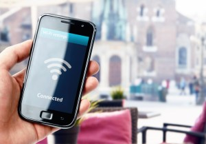 Hand holding smartphone with wi-fi connection in cafe