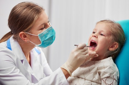 Woman dentist in mask doing teeth checkup of little girl in dental room. Health care and medicine concept.