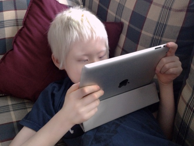 Boy holding screen close to eyes