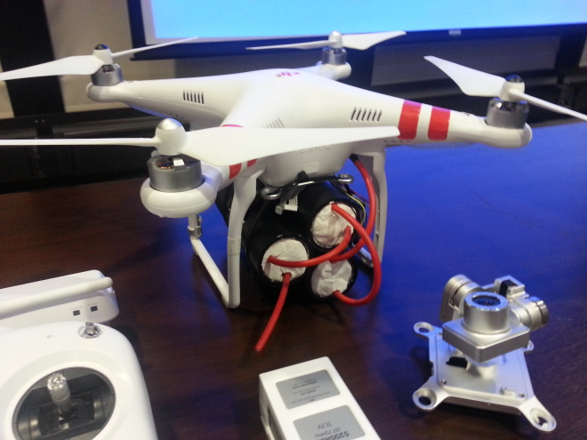 A Phantom 2 consumer drone is equipped with three pounds of mock explosive at a January 16 DHS conference.